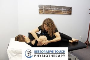 Hamilton Mountain Physiotherapy Clinic, Restorative Touch owner Marilena working on a patient's back while they are lying on their side on a table with the Restorative Touch Physiotherapy logo in the bottom center